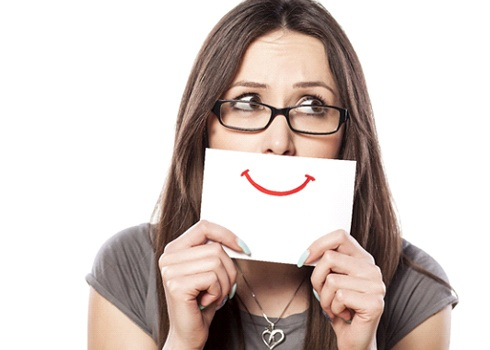 A woman holding up a card with a drawn on happy face in front of her mouth